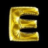 Goldener Buchstabe E gemacht vom aufblasbaren Ballon lokalisiert auf schwarzem Hintergrund Lizenzfreie Stockbilder