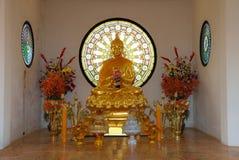 Goldener Buddha, der mit den Händen umklammert in der Betrachtung auf sitzt stockfotografie
