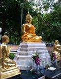Goldener Buddha und Schülerstatue im Park Stockfotos