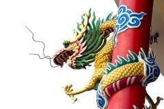 Goldener chinesischer Doppeldrache eingewickelt um roten Pol auf Isolathintergrund Stockfotografie