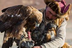 Goldener Eagle Hunter, bei der Jagd zu den Hasen, halten Steinadler auf seinen Armen lizenzfreie stockfotos