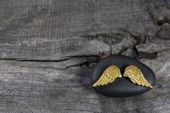 Goldener Engel beflügelt auf einen schwarzen Stein mit grauem hölzernem Hintergrund Stockbild