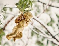 goldener Engel hängt Spielzeug auf einer schneebedeckten Niederlassung Stockfotos
