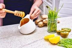 Goldener flüssiger organischer Honig auf einem Tropfenfänger, der grünen Weizen, Zitrone und Ingwer für einen Detox Smoothie gieß Stockfoto