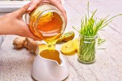 Goldener flüssiger organischer Honig, der aus Glas gießt Grüner Weizen, Zitrone und Ingwer für einen Detox Smoothie Lizenzfreies Stockbild