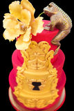 Goldener Frosch mit einer Blume auf rotem Kuchen an einem Hochzeitsfest Lizenzfreies Stockbild