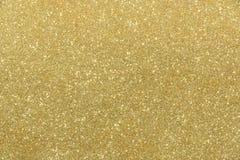 Goldener Funkelnbeschaffenheits-Zusammenfassungshintergrund Lizenzfreie Stockfotografie