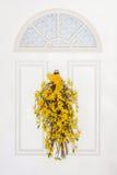 Goldener gelber Forsythie-Kranz, der an der weißen Tür hängt Lizenzfreie Stockfotos