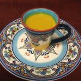 Goldener Gelbwurz Latte in der spanischen keramischen Kaffeetasse und der Platte Stockfotografie