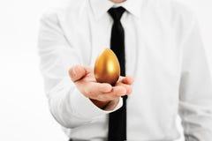 Goldener Geschäftsmann des Eies in der Hand Stockfotos