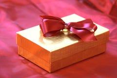 Goldener Geschenkkasten mit Bogen Stockfotos