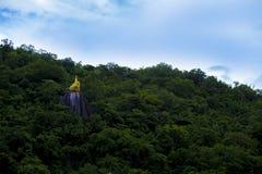 Goldener heiliger Felsen bei Wat Thewarup Song Tham, Thailand umgab durch Wald unter dem blauen Himmel Lizenzfreies Stockfoto