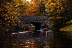 Goldener Herbstkanal mit einem Boot in der Mitte von Riga, Lettland stockfotos