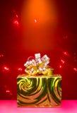 Goldener Kasten des Cristmas Geschenks auf rotem Hintergrund Stockfotografie