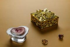 Goldener Kasten für Ringe und ein rotes Kerzenherz stockfotos