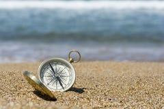 Goldener Kompass auf dem Strand stockfotos