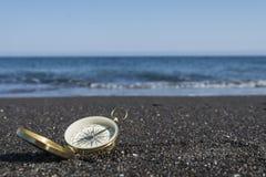 Goldener Kompass auf der Küste Fokus auf Kompass stockbild