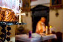 Goldener Kreuzabschluß oben, mit unscharfem Priester während der heiligen Masse Stockfotos