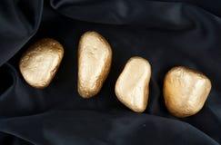 Goldener Luxusstein lokalisiert auf schwarzer Seide Goldkopfstein lizenzfreie stockfotos