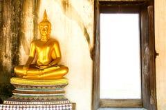 Goldener meditierender Buddha nahe bei Öffnungstür bei Wat Phutthaisaw Lizenzfreies Stockfoto