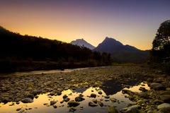 Goldener Momentsonnenaufgang mit Berg Stockfotos