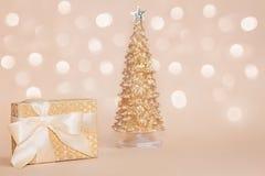Goldener Präsentkarton mit einem Seidenbogen gegen Goldfunkelnde Weihnachtskiefer auf Pastellhintergrund mit schönem stockfotografie