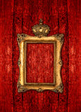 Goldener Rahmen mit Krone über rotem hölzernem Hintergrund Stockbilder