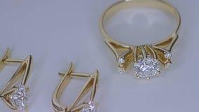 Goldener Ring mit einem Diamanten auf Weiß stock footage