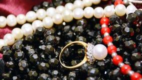 Goldener Ring mit Perle und Zirkon, auf einer schwarzen Halskette und Perlen von der roten Koralle der Weißperlen Lizenzfreie Stockfotos