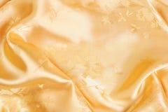 Goldener Satinhintergrund lizenzfreie stockfotos