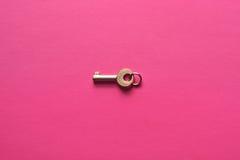 Goldener Schlüssel auf einem rosa Hintergrund Stockfotografie
