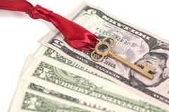 Goldener Schlüssel mit Bogen und Dollar Stockfotos