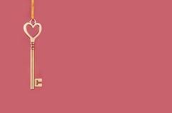 Goldener Schlüssel zum Hängen an einem rosa Hintergrund Stockfotos