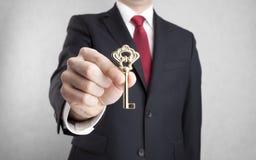 Goldener Schlüssel in der Geschäftsmannhand Stockfotografie