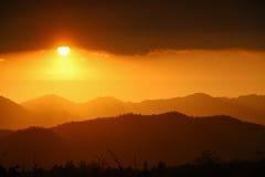 Goldener Sonnenuntergang über Berg und Wald Stockfotos