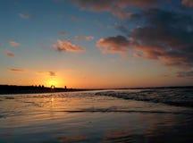 Goldener Sonnenuntergang über Küste des Meeres stockfotos