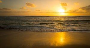 Goldener Sonnenuntergang als Rollen auf Ufer stockfotos
