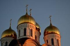 Goldener Sonnenuntergang auf den Hauben der Kirche Lizenzfreies Stockbild