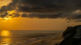 Goldener Sonnenuntergang an der felsigen Küste des Balinese stockbild