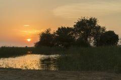 Goldener Sonnenuntergang in der Wüste Die Landschaft der Wüste und des Sees Stockfotografie