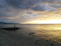 Goldener Sonnenuntergang mit Fischer Lizenzfreie Stockbilder