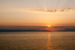 Goldener Sonnenuntergang mit Strahlen über den Wolken, horizontal Lizenzfreies Stockbild
