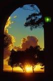 Goldener Sonnenuntergang unter einem Portal und grüne Straßenbeleuchtung Lizenzfreie Stockfotos