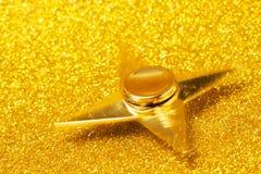 Goldener Spinner auf einem funkelnden Hintergrund Lizenzfreie Stockfotos