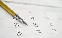 Goldener Stift auf Kalender stockbilder