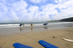 Goldener Strand mit den Kindern, die gehen zu surfen Lizenzfreie Stockfotografie
