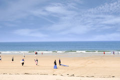 Goldener Strand mit den Leuten, die gehen zu surfen Lizenzfreie Stockbilder