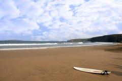 Goldener Strand mit einsamem Surfbrett Lizenzfreie Stockfotos