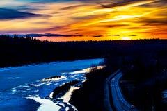 Goldener Stundensonnenuntergang ?ber gefrorenem Fluss Winter in Edmonton, Alberta, Kanada stockfotos