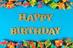 Goldener Text alles Gute zum Geburtstag und bunte Geschenke auf einem Blau lizenzfreie stockfotografie